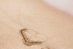 Het hart op het zand wordt geschilderd wordt gedeeltelijk gereinigd door de golf die stock fotografie