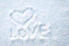 Het hart trekt op smow met de woordLIEFDE Stock Fotografie