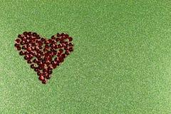 Het hart van het bronslovertje op flikkerende groene achtergrond Royalty-vrije Stock Fotografie