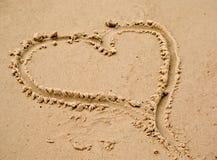Het hart van de liefde in het strandzand Stock Afbeeldingen
