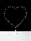 Het hart van de melk over zwarte Royalty-vrije Stock Foto's