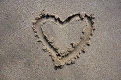 Het hart van de valentijnskaartendag op zand wordt getrokken dat Royalty-vrije Stock Foto's