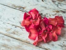 Het Hart van de valentijnskaartendag van Rode Rozenbloemblaadjes wordt gemaakt op uitstekende houten achtergrond die Ruimte voor  Royalty-vrije Stock Foto