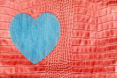Het hart van denim wordt gemaakt, ligt op de rode krokodilhuid die Royalty-vrije Stock Foto's
