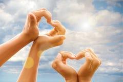 Het hart van gebaarhanden van op achtergrond van de hemel royalty-vrije stock afbeelding