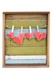 Het hart van het document het hangen op de drooglijn. Op oude houten achtergrond. Royalty-vrije Stock Afbeeldingen