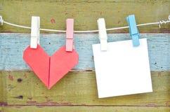 Het hart van het document het hangen op de drooglijn. Op oude houten achtergrond. Royalty-vrije Stock Foto's