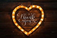 Het hart van lichten op een donkere achtergrond en de woorden danken u Royalty-vrije Stock Afbeeldingen