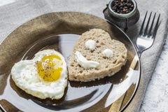 Het hart vormde gebraden ei en brood in een plaat, op een vastgestelde lijst Smiley op een stuk van brood royalty-vrije stock afbeeldingen