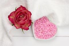 Het hart vormde kom met roze badzout dat wordt gevuld Stock Fotografie