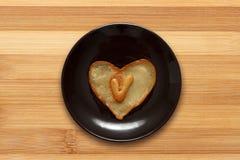 Het hart vormde pannekoek met brief V binnenkant op donkere bruine plaat op houten achtergrond Stock Afbeelding