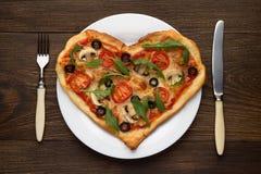 Het hart vormde pizza op witte plaat met vork en mes klaar te eten Italiaanse schotel voor Valentijnskaartendag op houten lijst Royalty-vrije Stock Afbeeldingen