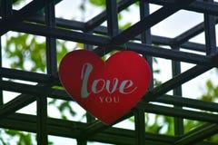 Het hart-vormige hangende teken in de binnenplaats is een rood hart royalty-vrije stock afbeeldingen