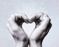 Het hart wordt gevormd door vrouwen` s handen Stock Afbeeldingen