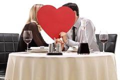 Het hartelijke paar kussen achter een hart stock foto