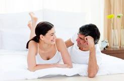 Het hartelijke paar op elkaar inwerken die op hun bed ligt Stock Fotografie