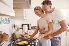 Het hartelijke Rijpe Paar bereidt Ontbijt samen in Keuken voor stock foto