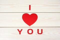 Het hartsymbool op een houten achtergrond met inschrijving I houdt van u Stock Afbeelding