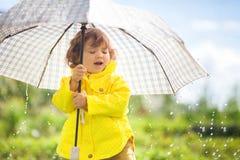 Het hebben van pret onder de regen, peutermeisje met paraplu Stock Afbeelding
