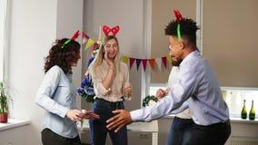 Het hebben van pret tijdens collectieve Nieuwjaarpartij in het bureau: Multiraciale groep gelukkige beambten die dansen tijdens stock footage
