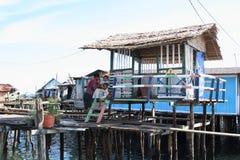 Het hebben van rust in schaduw van kleurrijke huizen boven overzees Royalty-vrije Stock Foto's