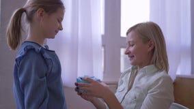 Het heden aan moeder, weinig dochter geeft het glimlachen teder mammaverjaardagsgeschenk en omhelzingen en verheugt zich thuis stock footage