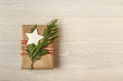 Het heden van de Kerstmisgift in duurzaam gerecycleerd verpakkend document met verse evergreens natuurlijke decoratie die wordt v royalty-vrije stock afbeelding