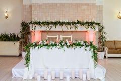 Het is heel wat kaarsen en greens dichtbij een lijst van de bruidegom en de bruid royalty-vrije stock afbeelding
