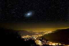 Het heelal boven stadslichten. Stock Fotografie