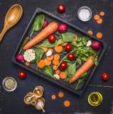 Het heerlijke assortiment van landbouwbedrijf verse groenten sneed wortelen, verse spinaziebladeren, kruiden en boter, kers tomat Stock Fotografie