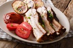 Het heerlijke borststuk van het braadstukvarkensvlees met aardappelhuiden, tomaten en sau Stock Foto