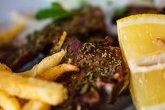 Het heerlijke Dienen van Succulent Geroosterd Groot die Riblapje vlees met Mediterrane Kruiden naast Frieten en Citroenplak wordt Royalty-vrije Stock Afbeeldingen
