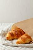 Het heerlijke Frans bakte vers croissants in document zak op een textielachtergrond Royalty-vrije Stock Foto