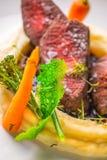 Het heerlijke hertevleeslapje vlees met aardappels stampt en groenten op witte plaat, productfotografie voor exclusief restaurant stock afbeelding