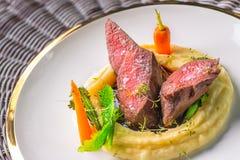 Het heerlijke hertevleeslapje vlees met aardappels stampt en groenten op witte plaat, productfotografie voor exclusief restaurant stock afbeeldingen