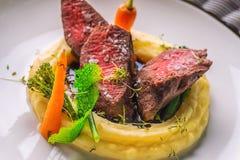 Het heerlijke hertevleeslapje vlees met aardappels stampt en groenten op witte plaat, productfotografie voor exclusief restaurant royalty-vrije stock foto's