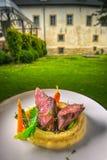 Het heerlijke hertevleeslapje vlees met aardappels stampt en groenten op witte plaat, productfotografie voor exclusief restaurant stock fotografie