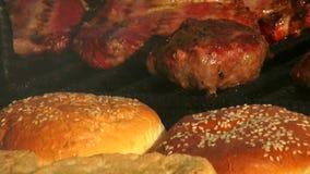 Het heerlijke lapje vlees van het voedsel hete vlees met een hamburgerbroodje op een grill stock video