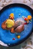 Het heerlijke zoete chocoladefondantje met fruit diende op blauwe plaat, productfotografie voor restaurant of patisserie stock afbeeldingen