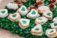 Het heerlijke zoete kleurrijke dessert van koekjesharten groen en wit voor verjaardagspartij op een suikergoedbar royalty-vrije stock fotografie