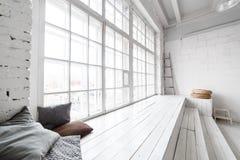Het heldere binnenland van de fotostudio met groot venster, hoog plafond, witte houten vloer royalty-vrije stock afbeeldingen