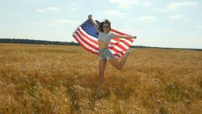 Het heldere gebied van de de herfsttarwe met meisje het lopen snel met Amerikaanse vlag stock footage