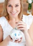 Het heldere geld van de vrouwenbesparing in een piggy-bank Royalty-vrije Stock Afbeeldingen