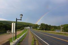 Het heldere regenboog uitrekken zich in de hemel over het kleine dorp van Mabou in landelijke Kaap Breton stock afbeelding