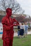 Het heldere rode mannelijke het leven standbeeld rolt glasbal in palm van hand Stock Foto