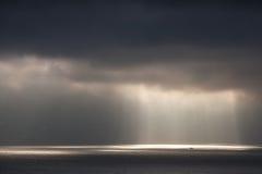 Het heldere zonlicht gaat door donkere stormachtige wolken Royalty-vrije Stock Afbeeldingen