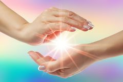 Het helen van handen met heldere zonnestraal op regenboogachtergrond stock fotografie
