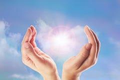 Het helen van handen met heldere zonnestraal op regenboogachtergrond royalty-vrije stock afbeelding