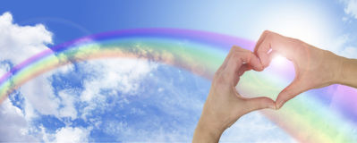 Het helen van handen op blauwe hemel en regenboogbanner Royalty-vrije Stock Fotografie