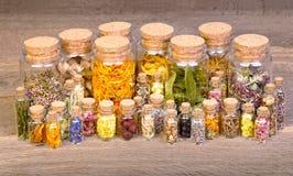 Het helen van kruiden in flessen voor kruidengeneeskunde op oude houten lijst stock foto's